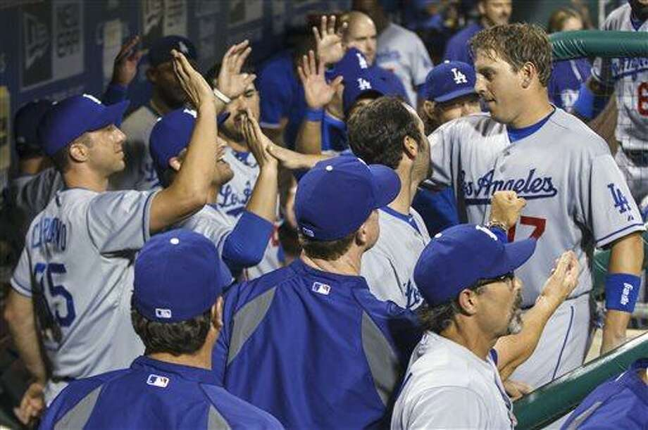 Los Angeles Dodgers' A.J. Ellis gets congratulations from teammates after scoring on a double by Mark Ellis against Philadelphia Phillies during the seventh inning of a baseball game, Friday, Aug. 16, 2013, in Philadelphia. The Dodgers won 4-0. (AP Photo/Christopher Szagola) Photo: AP / FR170982 AP