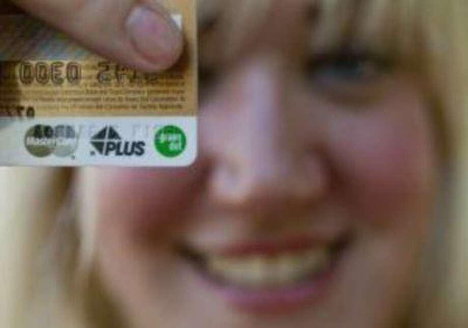 Receptionist Erin Gamboa holds her Green Dot prepaid debit card, June 2011 in Monrovia, Calif. (Damian Dovarganes / AP) Photo: AP / AP net