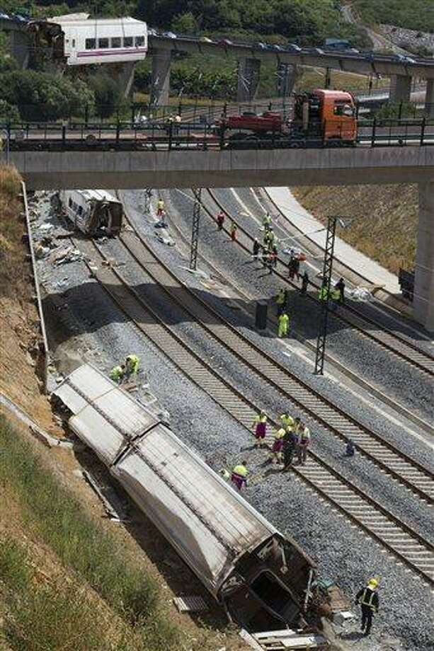 Derailed cars are removed as emergency personnel work at the site of a train accident in Santiago de Compostela, Spain, on Thursday, July 25, 2013. An Associated Press analysis of video images shows that a Spanish train was traveling well above the speed limit when it derailed, killing at least 80 people. Officials say the speed limit on that section of track is 80 kph (50 mph). (AP Photo/ Lalo Villar) Photo: ASSOCIATED PRESS / A2013