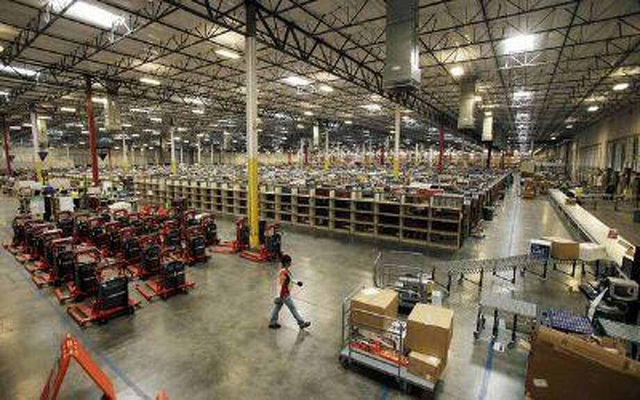 """File-In this Monday, Nov. 16, 2009 file photo, a view inside the 800,000 sq. ft. <a href=""""http://Amazon.com"""">Amazon.com</a> distribution and fulfillment center warehouse in Goodyear, Ariz. <a href=""""http://Amazon.com"""">Amazon.com</a> Inc. says it is adding 7,000 jobs in 13 states, beefing up staff at the warehouses where it fills orders, and in its customer service division. The company says it will add 5,000 full-time jobs at its U.S. distribution centers, which currently employ about 20,000 workers who pack and ship customer orders. (AP Photo/Ross D. Franklin, File) Photo: AP / AP net"""