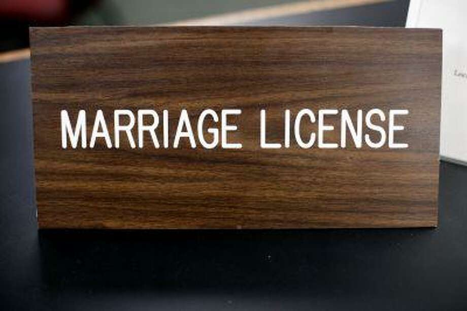 "A placard on a desk reading ""marriage license"" is at a Montgomery County office, Wednesday, July 24, 2013, in Norristown, Pa. Photo: AP / AP"
