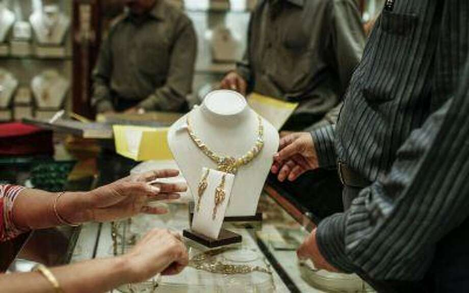 """A clerk shows a gold necklace to a customer at the Dwarkadas Chandumal Jewelers in Mumbai in May. India just increased taxes on gold imports to tackle a record current-account deficit and now, says the head of a trade group, """"Smuggling of gold will increase and the organized industry will be in disarray."""" (Dhiraj Singh/Bloomberg)"""