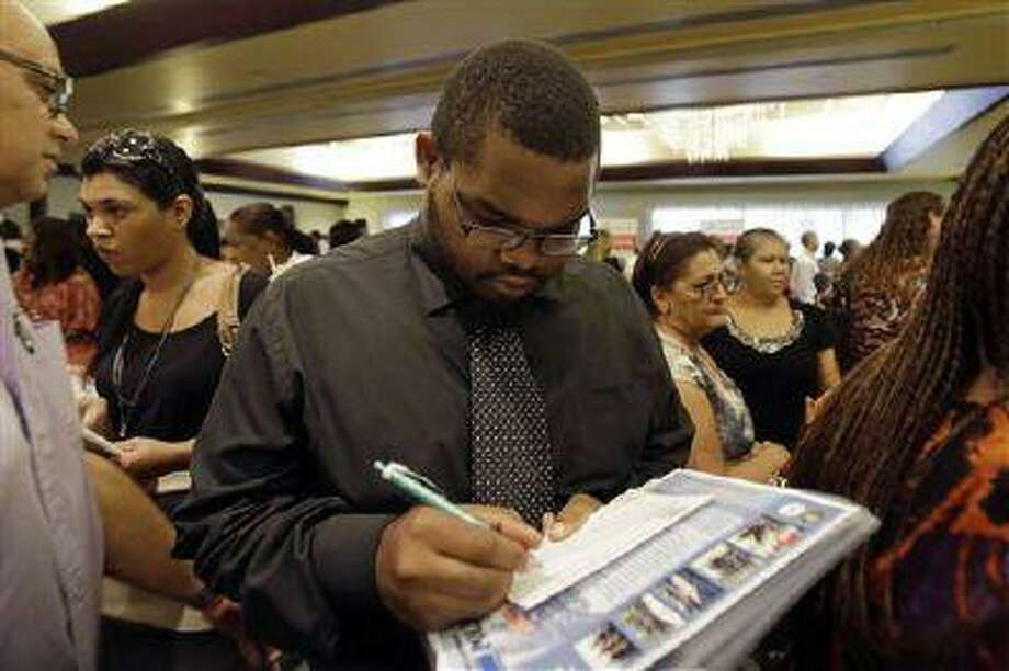 In this Wednesday, Aug., 14, 2013, photo, job seeker Kelsey Devoe, of Miramar, Fla., fills out a contact form at a job fair in Miami Lakes, Fla. The Labor Department reports on the number of Americans who applied for unemployment benefits last week on Thursday, Aug. 15. (Alan Diaz/AP) Photo: AP / AP