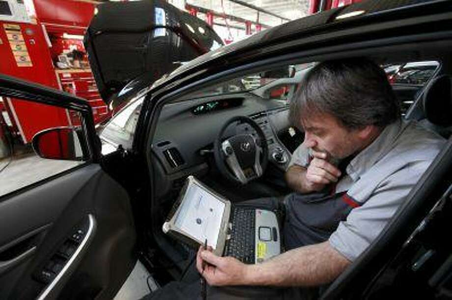 Master Diagnostic Technician Kurt Juergens, of Foxborough, Mass., uses a laptop computer to diagnose and repair the brake system on a 2010 Toyota Prius in the repair shop of a Toyota dealership, in Norwood, Mass., Feb. 9, 2010. Photo: ASSOCIATED PRESS / AP2010