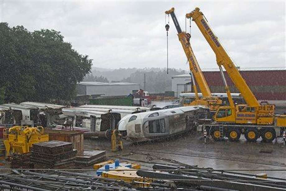 Part of the wreckage of the crashed train is seen in a crane depository on the outskirts of Santiago de Compostela, Spain, Sunday July 28, 2013. Spain's interior minister Jorge Fernandez Diaz says the driver whose speeding train crashed, killing 78 people, is now being held on suspicion of negligent homicide. The Spanish train derailed at high speed Wednesday killing and injuring dozens. (AP Photo/Lalo R. Villar) Photo: AP / AP