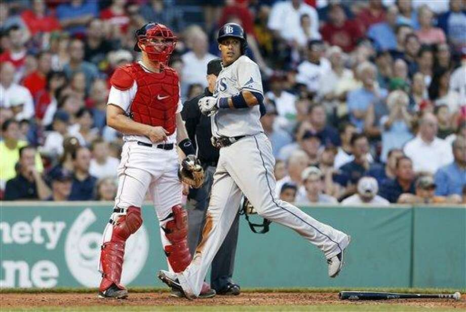 Tampa Bay Rays' Yunel Escobar, right, looks back beside Boston Red Sox's Ryan Lavarnway as he scores on a run-run double by Sean Rodriguez in the fourth inning of a baseball game in Boston, Monday, July 29, 2013. (AP Photo/Michael Dwyer) Photo: AP / AP