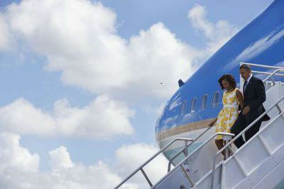 President Barack Obama and first lady Michelle Obama arrive in Orlando where they are expected to speak at a disabled veterans event in Orlando, Fla., Saturday, Aug. 10, 2013. After the event at the Disabled American Veterans National Convention the Obamas will travel to Martha's Vineyard, Mass. to begin their family vacation. (AP Photo/Jacquelyn Martin) Photo: AP / AP