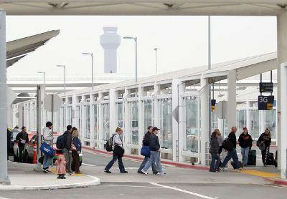 Passengers are seen outside Terminal 2 at Oakland International Airport in Oakland, Calif. on Wednesday, Jan. 9, 2013. Photo: JANE TYSKA / THE OAKLAND TRIBUNE/BAY AREA NEWS GROUP
