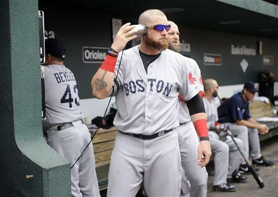 Boston Red Sox's Jonny Gomes plays with a can attached to a string leading to the dugout phone before a baseball game against the Baltimore Orioles, Sunday, July  28, 2013, in Baltimore. (AP Photo/Nick Wass) Photo: AP / FR67404 AP