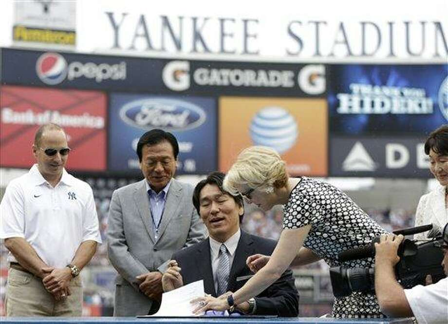 Yankees general manager Brian Cashman, far left, and Masao Matsui, father of Hideki Matsui, look on as 2009 World Series MVP Hideki Matsui signs his retirement papers with Yankees assistant general manager Jean Afterman in a home plate ceremony before the Yankees 55th baseball game of the year, Sunday, July 28, 2013, in New York. (AP Photo/Kathy Willens) Photo: AP / AP