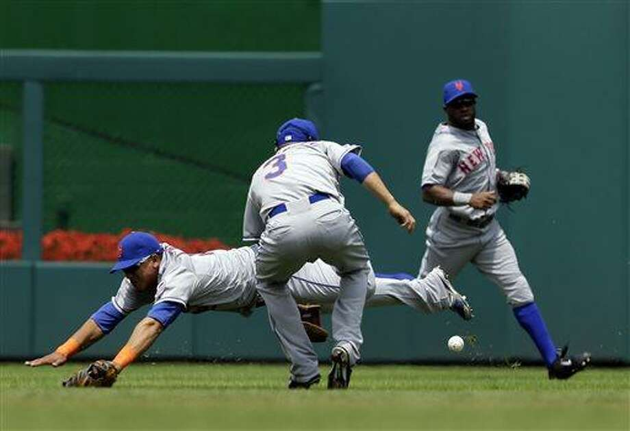 New York Mets center fielder Juan Lagares dives after a ball hit by Washington Nationals' Ryan Zimmerman during the first inning of a baseball game at Nationals Park Sunday, July 28, 2013, in Washington. Mets shortstop Omar Quintanilla (3) and left fielder Eric Young Jr., right, participate in the play. (AP Photo/Alex Brandon) Photo: AP / AP