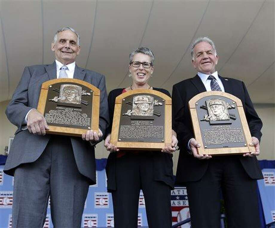 Family representatives Jerry Watkins, left, great grandson of Baseball Hall of Fame inductee Deacon White, Anne Vernon,center, great grandniece of inductee Jacob Ruppert, and Dennis McNamara, grandnephew of inductee Hank O'Day, hold the players' plaques after a ceremony on Sunday, July 28, 2013, in Cooperstown, N.Y. (AP Photo/Mike Groll) Photo: AP / AP