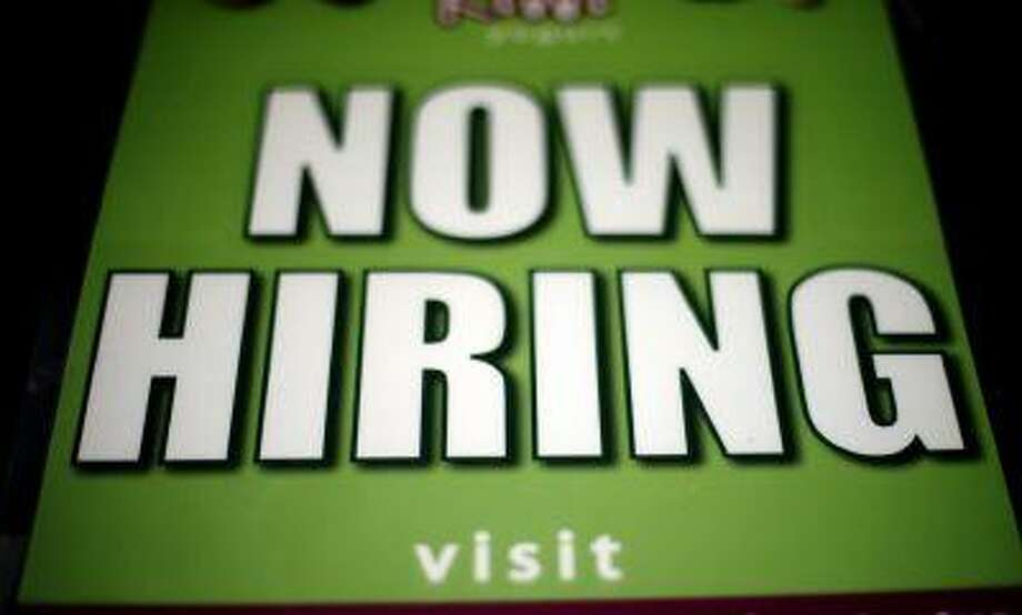 In this Friday, March 29, 2013, photo a storefront displaying a now hiring sign is placed on a window in Philadelphia. (Associated Press/Matt Rourke) Photo: AP / AP