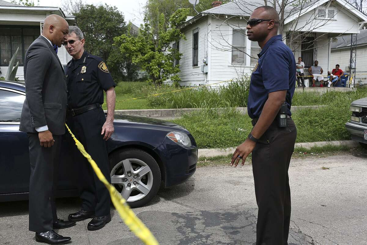Then-District 2 City Councilman Alan Warrick, left, talks with San Antonio Police Chief William McManus and SAPD spokesman Douglas Greene, right, at the scene of a shooting in March 2016 on the East Side. Warrick had pushed for ShotSpotter, a gunfire detection system that the city is now discontinuing.