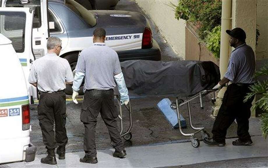 Miami-Dade morgue workers carry out a body out at the scene of a fatal shooting in Hialeah, Fla., Saturday, July 27, 2013. A gunman holding hostages inside the apartment complex killed six people before being shot to death by a SWAT team that stormed the building early Saturday following an hours-long standoff, police said. (AP Photo/Alan Diaz) Photo: AP / AP