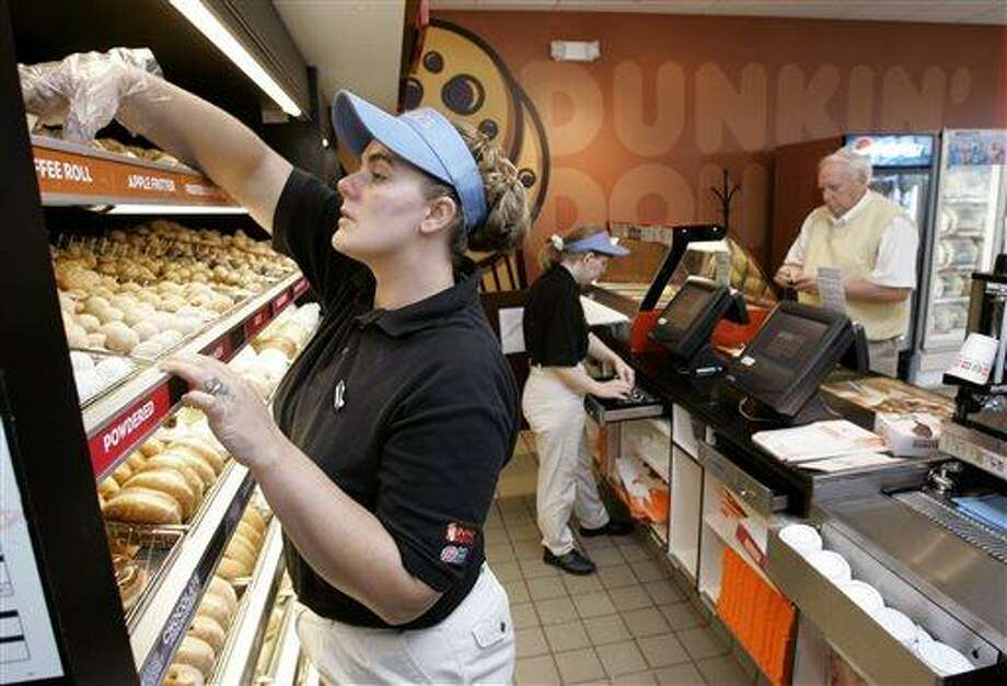 Frankie Morris, left, fills a costumer's order at the Dunkin' Donuts store, in Franklin, Tenn. Dunkin' Donuts offers seniors who purchase a large or extra-large beverage a free doughnut, but you have to show your AARP card. Associated Press file photo Photo: AP / AP