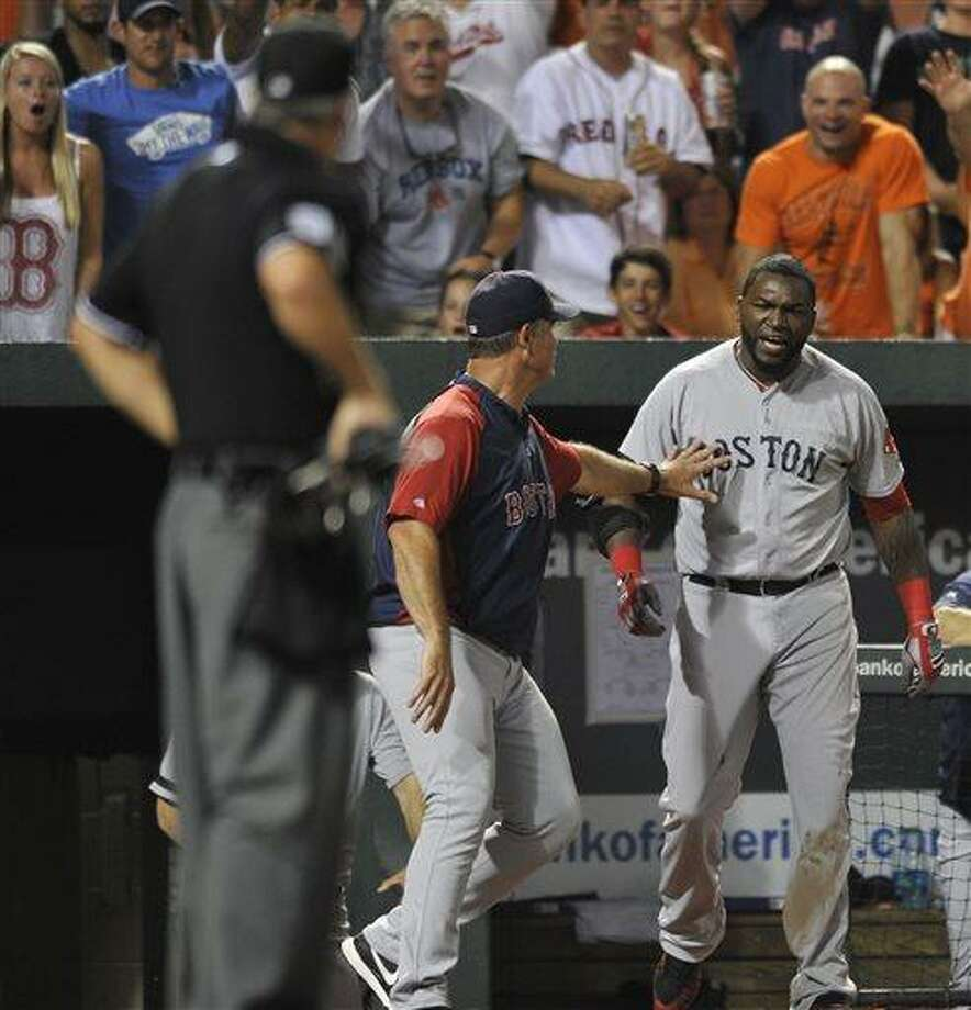 Boston Red Sox designated hitter David Ortiz, right, reacts and is held back by manager John Farrell after being ejected by home plate umpire Tim Timmons, left, in a baseball game against the Baltimore Orioles, Saturday, July 27, 2013, in Baltimore. (AP Photo/Gail Burton) Photo: AP / FR4095 AP