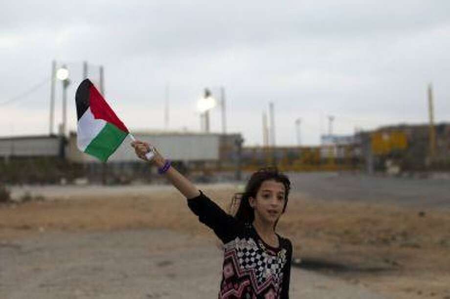 A Palestinian girl from the Israeli occupied West Bank waves the national flag as sh and others wait close to the Israeli military prison of Ofer, in the village of Betunia, for the release of Palestinian prisoners on August 13, 2013. Photo: AFP/Getty Images / 2013 AFP