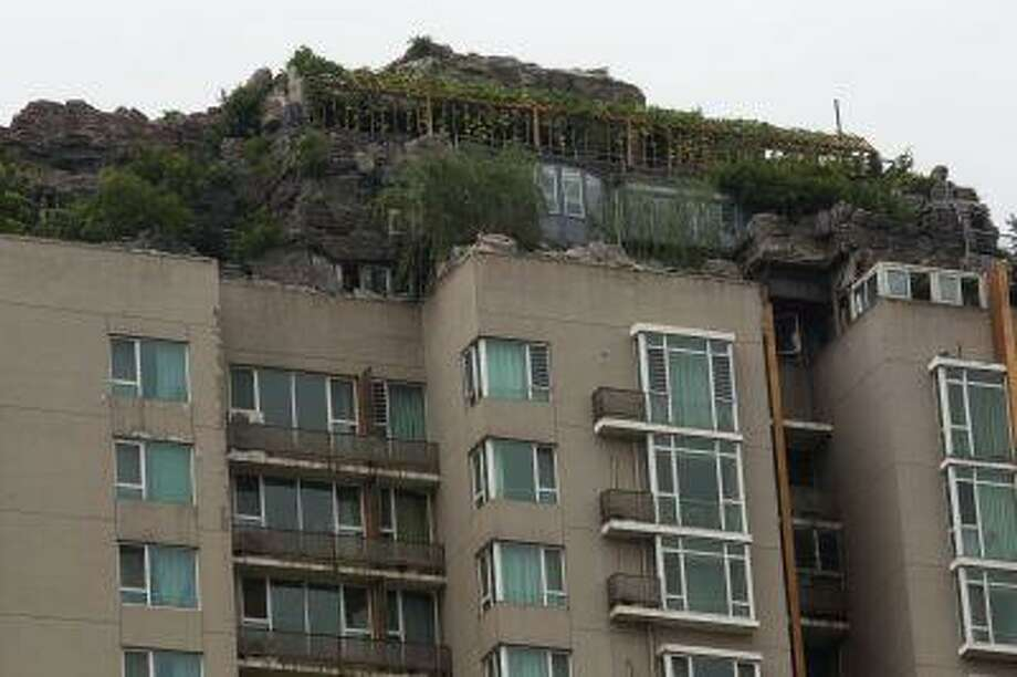A rooftop villa complete with rocks and flora built on top of a high rise residential building stands in Beijing, China, Aug. 13. Photo: ASSOCIATED PRESS / AP2013