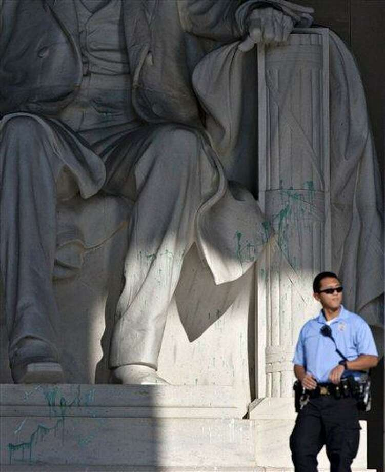 A U.S. Park Police officer stands guard next to the statue of Abraham Lincoln at the memorial in Washington, Friday, July 26, 2013, after the memorial was closed to visitors after someone splattered green paint on the statue and the floor area. Police say the apparent vandalism was discovered early Friday morning. No words, letters or symbols were visible in the paint. (AP Photo/J. Scott Applewhite) Photo: AP / AP