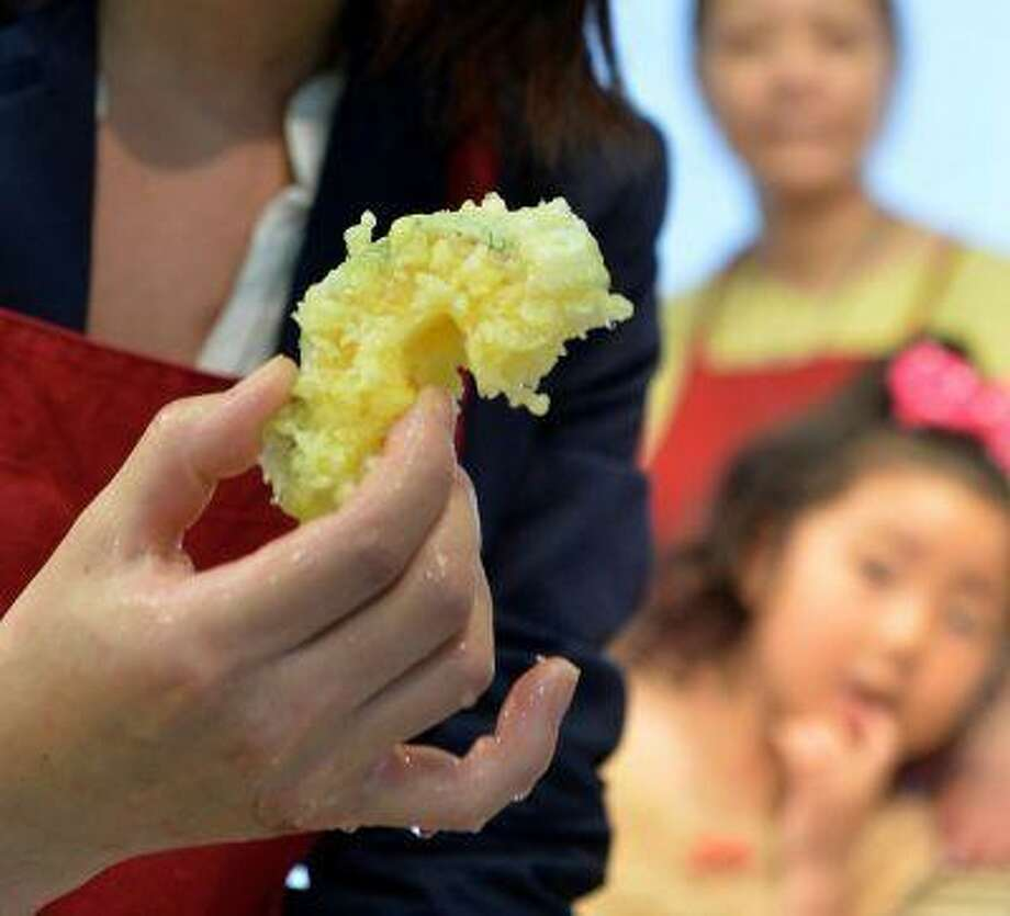 "A visitor shows off a fake food ""Tempura"" made of the wax at a workshop in Tokyo on May 28, 2013. The company opened two shops in Tokyo where it sells sushi cell-phone charms and bacon-adorned key chains -- all with multilingual signs warning that ""this is not edible"". The shops also let visitors take a stab at creating their own fake food. (AFP PHOTO / KAZUHIRO NOGI)"