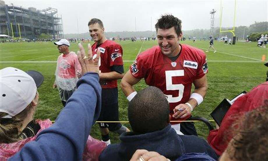 New England Patriots quarterbacks Tim Tebow, right, and Tom Brady talk with fans and sign autographs following practice at NFL football training camp in Foxborough, Mass., Friday, July 26, 2013. (AP Photo/Charles Krupa) Photo: AP / AP
