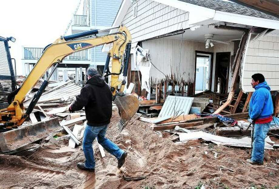 Peter Casolino - Register file photo: Workers begin knocking down a heavily damaged house along Ellis Road in East Haven after Superstorm Sandy.