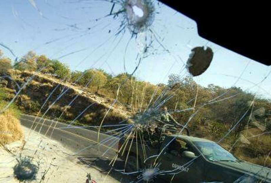 Mexican Army soldiers passing by are seen through the bullet-riddled windshield of a truck in Apatzingan, Michoacan State, Mexico, on December 12, 2010. Photo: AFP/Getty Images / 2010 AFP