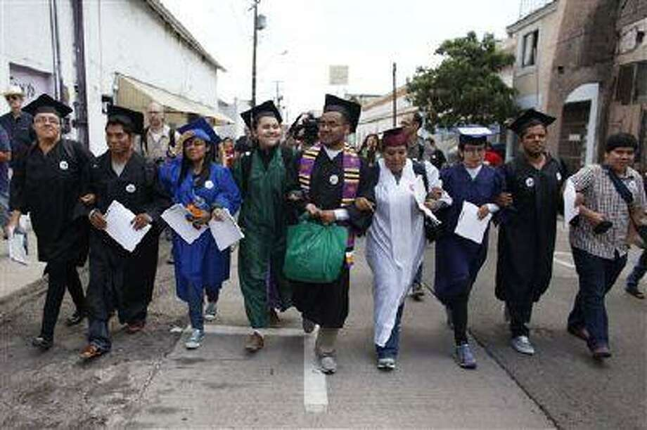 In this July 22, 2013 file photo, immigration rights activists, wearing their school graduation caps and gowns to show their desire to finish school in the U.S., march with linked arms to the U.S. port of entry where they planned to request humanitarian parole in Nogales, Mexico. (Samantha Sais/AP file) Photo: AP / AP