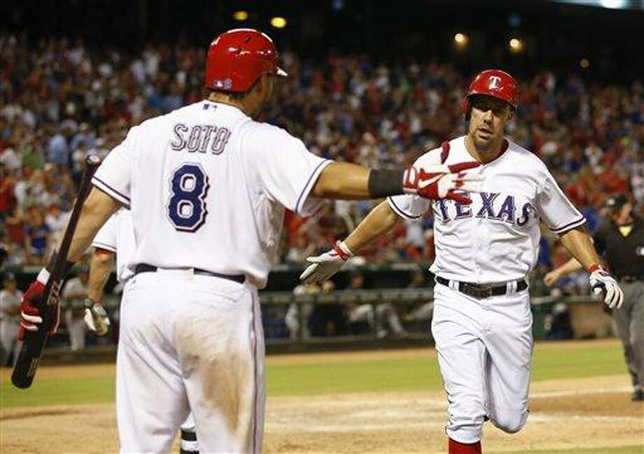 Texas Rangers' David Murphy, right, is congratulated by Geovany Soto (8) after his solo home run against the New York Yankees during the eighth inning of a baseball game, Wednesday, July 24, 2013, in Arlington, Texas. The Rangers won 3-1. (AP Photo/Jim Cowsert) Photo: AP / FR170531 AP