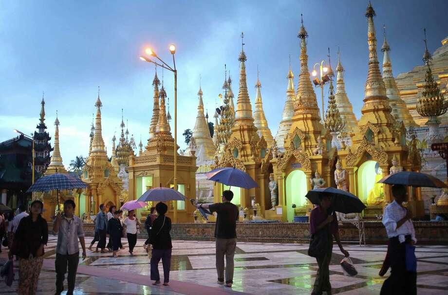 Visitors make their way around the Shwedagon Pagoda despite the rainy weather in Yangon, Myanmar, Sunday, Aug. 11, 2013. The Shwedagon Pagoda is the most sacred Pagoda to the Burmese.(AP Photo/Wong Maye-E) Photo: ASSOCIATED PRESS / AP2013
