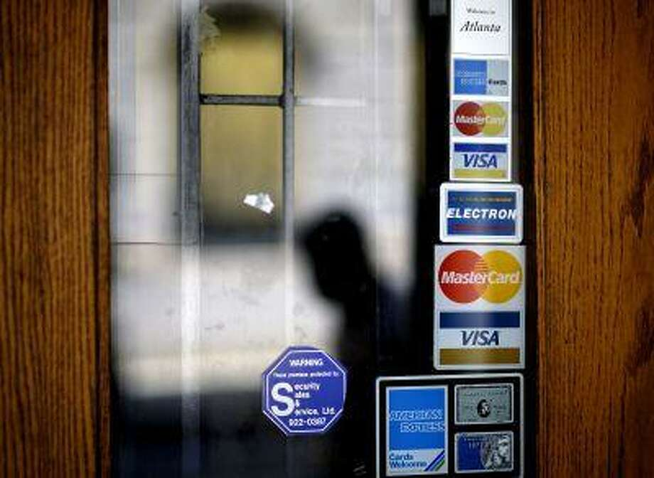 Credit card logos are seen on a downtown storefront as a pedestrian passes in Atlanta. (AP Photo/David Goldman, File) Photo: ASSOCIATED PRESS / A2012