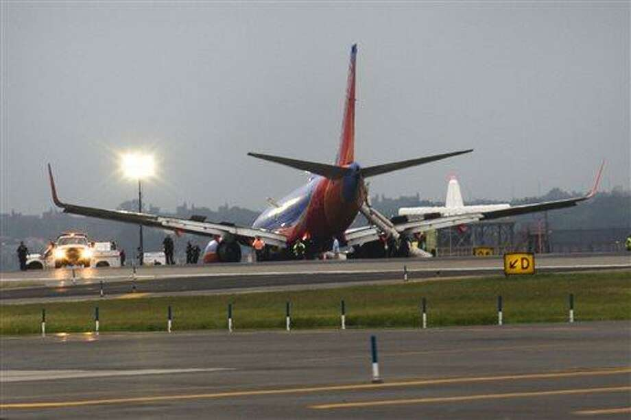 A southwest airlines plane rests on the tarmac  after what officials say was a nose gear collapse during a landing at LaGuardia Airport, Monday, July 22, 2013, in New York. The Federal Aviation Administration says the plane landed safely. (AP Photo/John Minchillo) Photo: AP / FR170537 AP