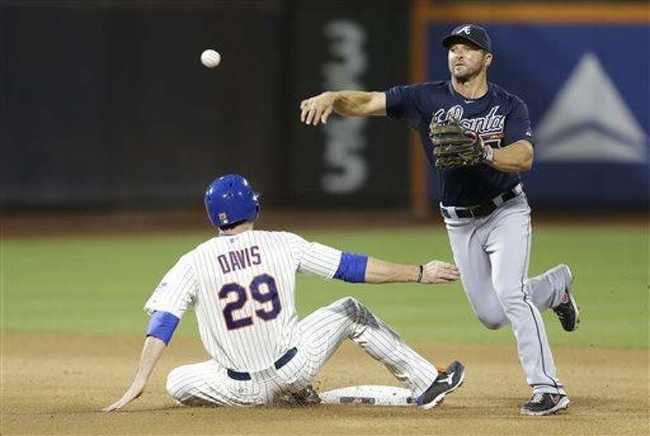 Atlanta Braves second baseman Dan Uggla (26) throws to first after forcing out New York Mets Ike Davis (29) after the Mets John Buck hit into a fourth-inning double play in a baseball game, Monday, July 22, 2013, in New York. (AP Photo/Kathy Willens) Photo: AP / AP