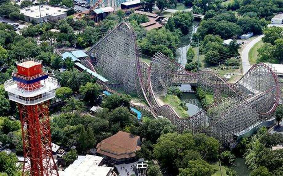This aerial photo shows the Texas Giant roller coaster at  Six Flags Over Texas where a woman fell to her death, Saturday, July 20, 2013, in Arlington, Texas. Investigators will try to determine if a woman who died while riding the roller coaster at the amusement park Friday night fell from the ride after some witnesses said she wasn't properly secured. (AP Photo/The Dallas Morning News, Louis DeLuca)  MANDATORY CREDIT; MAGS OUT; TV OUT; INTERNET USE BY AP MEMBERS ONLY; NO SALES Photo: AP / The Dallas Morning News