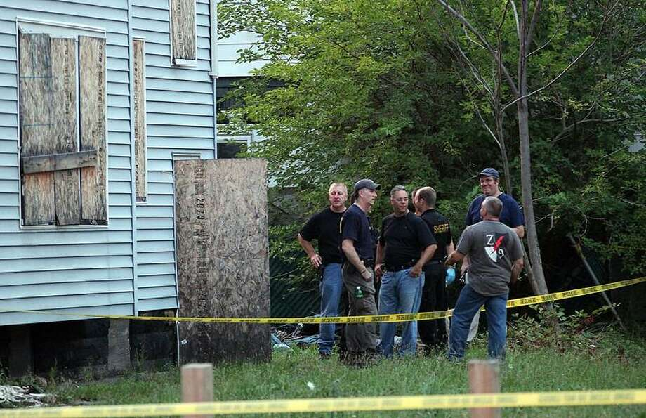 Law enforcement and FBI stand at the back of a boarded-up home where bodies were found earlier in the day Saturday, July 20, 2013 in East Cleveland, Ohio. Police say three bodies have been found in plastic bags in East Cleveland. Police Commander Mike Cardilli said a woman's body was found Friday in a garage and two other bodies were found Saturday _ one in a backyard and the other in the basement of a vacant house.  (AP Photo/The Plain Dealer, Joshua Gunter) Photo: AP / The Plain Dealer