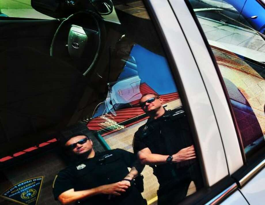 New Haven police officers Decrezenzo  (L) and Mac are leading the department for gun arrests this year 7/17.  They are reflected in their car, in front of the Fair Haven sub station. Melanie Stengel/New Haven Register