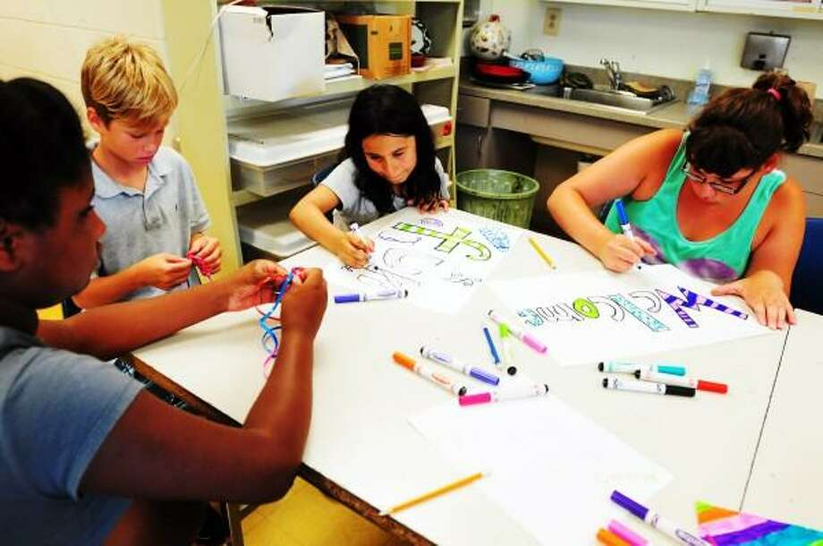 Left to right:  Janazria Cooks of Shelton, 10; Dmitri Nichio of Shelton, 11, Gypsy Saez of Shelton, 9, and Kaitylyn Esposito during an arts and crafts session at the  Boys and Girls Club of the Lower Naugatuck Valley in Shelton, Conn. Monday July 16, 2013. Peter Hvizdak/New Haven Register Photo: New Haven Register / ©Peter Hvizdak /  New Haven Register
