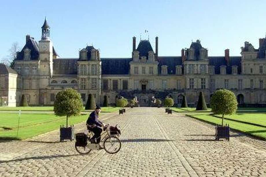 "FILE - In this Nov.15 2001 file photo, a postman rides his bicycle past the Fontainebleau castle, outside Paris. The palace dominating the town of Fontainebleau is ""the house of centuries, the home of kings."" Sundays are good for exploring these mansions and munching on pack lunches on the grounds. (AP Photo/Laurent Rebours, File) Photo: AP / AP"