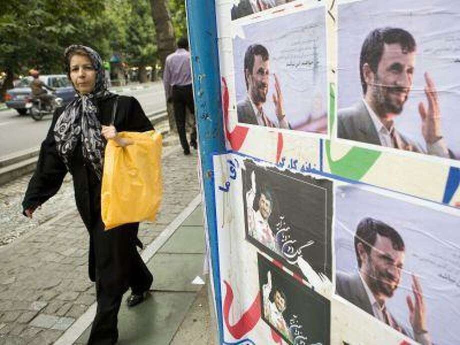 A women walks past posters for President Mahmoud Ahmadinejad in Tehran in June 2009. Photo: BLOOMBERG NEWS / BLOOMBERG