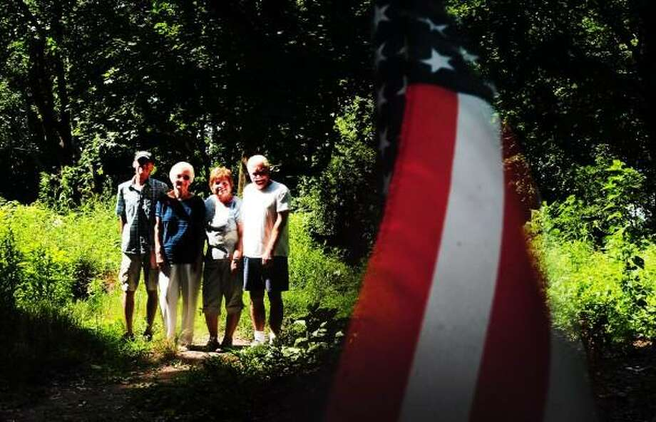 Friends of Fort Wooster from left to right: Kevin Maher of New Haven,co-chairman;  Marge Ottenbreit of New Haven, co-chairman; Sue Marchese of Wallingford; and Tom Holman of New Haven stand near the powder of cellar of Fort Wooster at Fort Wooster Park on Beacon Ave in New Haven Wednesday July 31, 2013.  The flag is placed near Fort Wooster every time Marchese works at the site because she believes the place is sacred because of its Revolutionary War era importance. Peter Hvizdak - Register Photo: New Haven Register / ©Peter Hvizdak /  New Haven Register