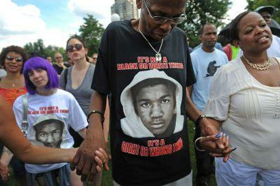 """DENVER, CO - JULY 14: Emmitt Brooks, middle, lowers his head in prayer while holding hands with a Charnissa Staten, far right, near the end of the rally in City Park in Denver, CO on July 14, 2013. Several hundred people turned out to show their disappointment in the acquittal of George Zimmerman in the murder trail of Trayvon Martin. Zimmerman is the Florida man who shot and killed Trayvon Martin. """"We will not erase the conversation of race,"""" said Jeff Fard, founder of Brother Jeff's Cultural Center in the Five Points neighborhood. """"Don't be afraid to say if Trayvon Martin was a white man he would be alive today."""" Photo by Helen H. Richardson/The Denver Post) Photo: DP / Copyright - 2013 The Denver Post, MediaNews Group."""
