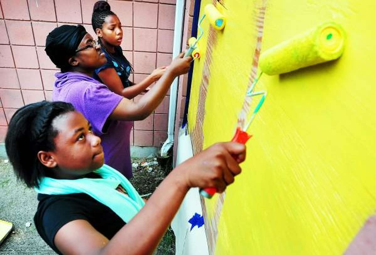 Front to back, Emani Adams, 14, Jasmine Peterson, 19, and Tatyana Herbert, 14, of Solar Youth paint over plywood on a boarded up apartment at Westville Manor Housing in New Haven for a service project on 8/1/2013. Arnold Gold - Register