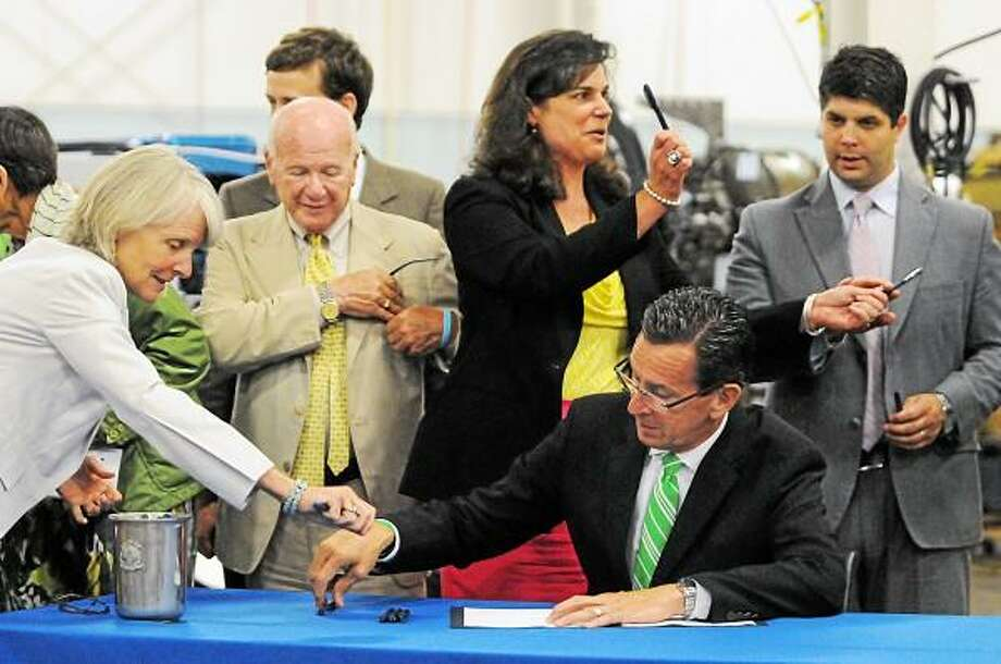 Catherine Avalone - The Middletown Press  Dannel P. Malloy signs legislation Public Act 13-56 - ACC which will assist small businesses in Connecticut pursuing global commerce which will help promote more Connecticut products into foreign markets Monday afternoon at Test Logic at 17 Kenneth Dooley Drive in Middletown. / TheMiddletownPress