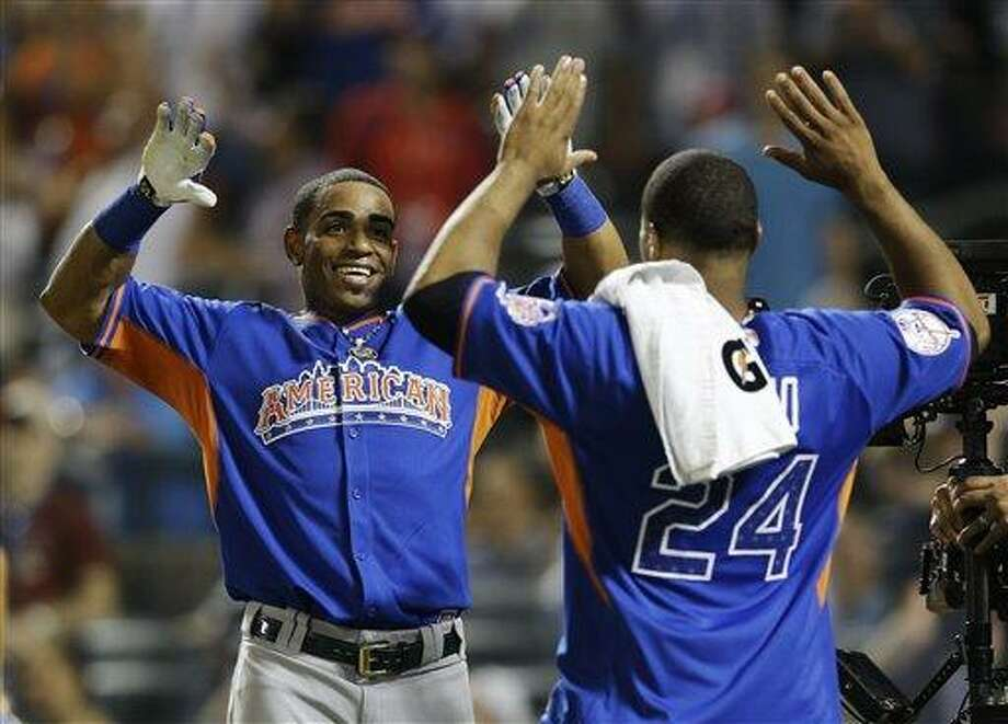American League's Yoenis Cespedes, left, of the Oakland Athletics, celebrates with Robinson Cano after winning the  MLB All-Star baseball Home Run Derby, on Monday, July 15, 2013 in New York. (AP Photo/Kathy Willens) Photo: AP / AP