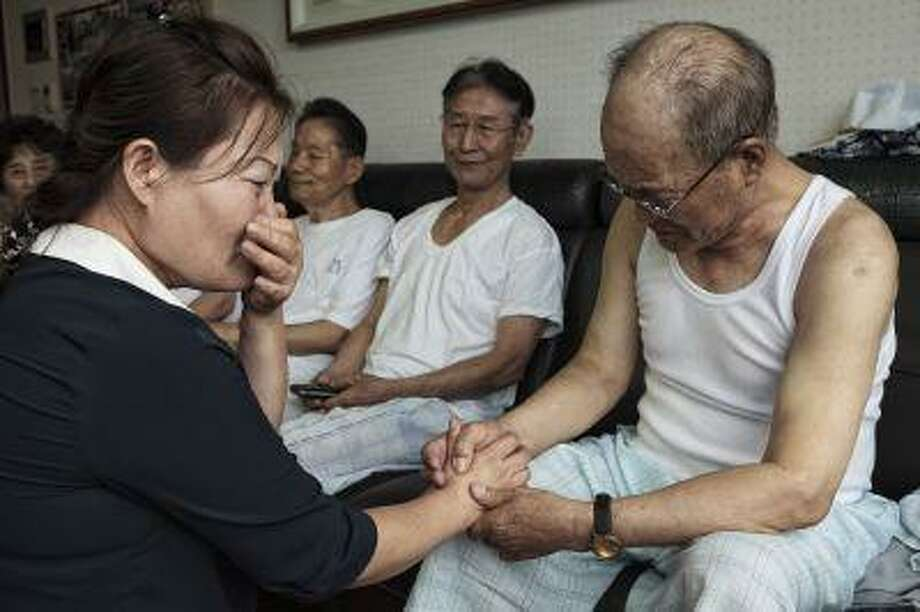 Kim Kyung-hee, 40, bursts into tears as she speaks with Lee Sun-woo, 82, on Wednesday in Seoul. Lee was captured by Chinese Communists in July 14, 1953, 13 days before the Korean War armistice was signed, and detained as a prisoner to work in a coal mine until he escaped from North Korea in 2006. Kim escaped from North Korea in 2012; her late father, Kim Woo-yong, worked in the same coal mine as Lee from 1953 to 2004. Lee and Kim met each other Wednesday for the first time since their escapes from North Korea. Photo: The Washington Post / The Washington Post