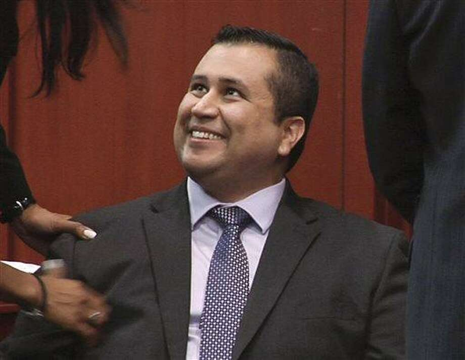 In this image from video, George Zimmerman smiles after a not guilty verdict was handed down in his trial at the Seminole County Courthouse, Sunday, July 14, 2013, in Sanford, Fla. Neighborhood watch captain George Zimmerman was cleared of all charges Saturday in the shooting of Trayvon Martin, the unarmed black teenager whose killing unleashed furious debate across the U.S. over racial profiling, self-defense and equal justice.  (AP Photo/TV Pool) Photo: ASSOCIATED PRESS / AP2013