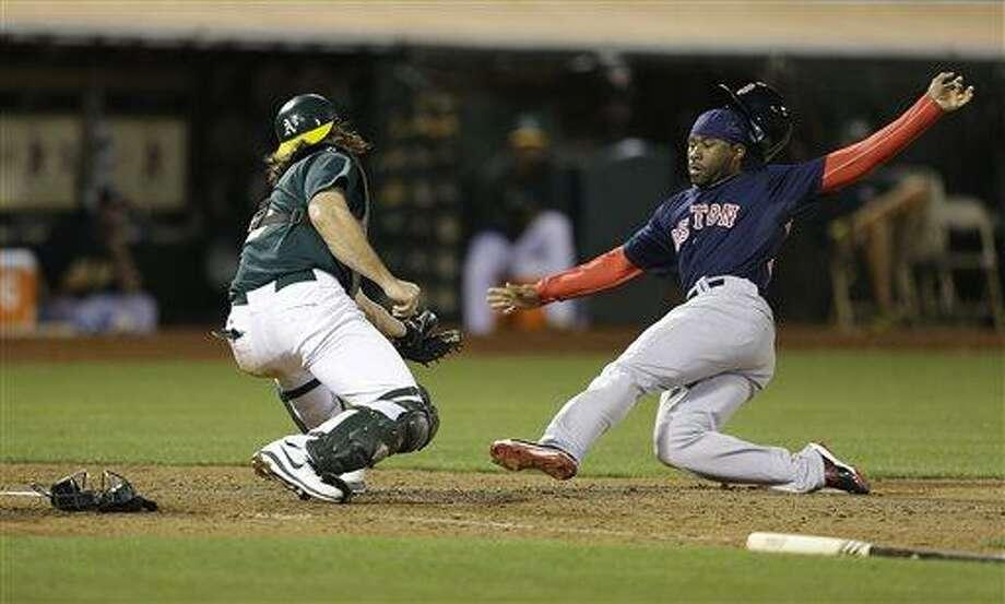 Boston Red Sox's Jackie Bradley Jr., right, slides as Oakland Athletics catcher John Jaso prepares to tag him out in the ninth inning of a baseball game Friday, July 12, 2013, in Oakland, Calif. (AP Photo/Ben Margot) Photo: AP / AP