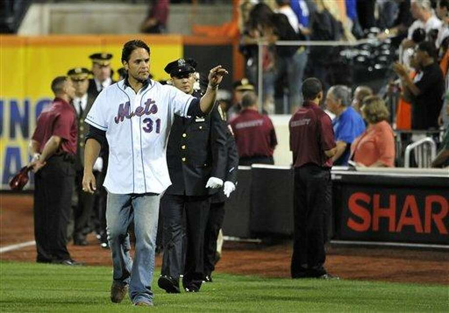 Former New York Mets catcher Mike Piazza leads a procession of first responders onto the field for a Sept. 11 remembrance ceremony before the New York Mets baseball game against the Chicago Cubs at Citi Field in New York, Sunday, Sept. 11, 2011. Franco threw out the ceremonial first pitch. (AP Photo/Kathy Kmonicek) Photo: ASSOCIATED PRESS / AP2011