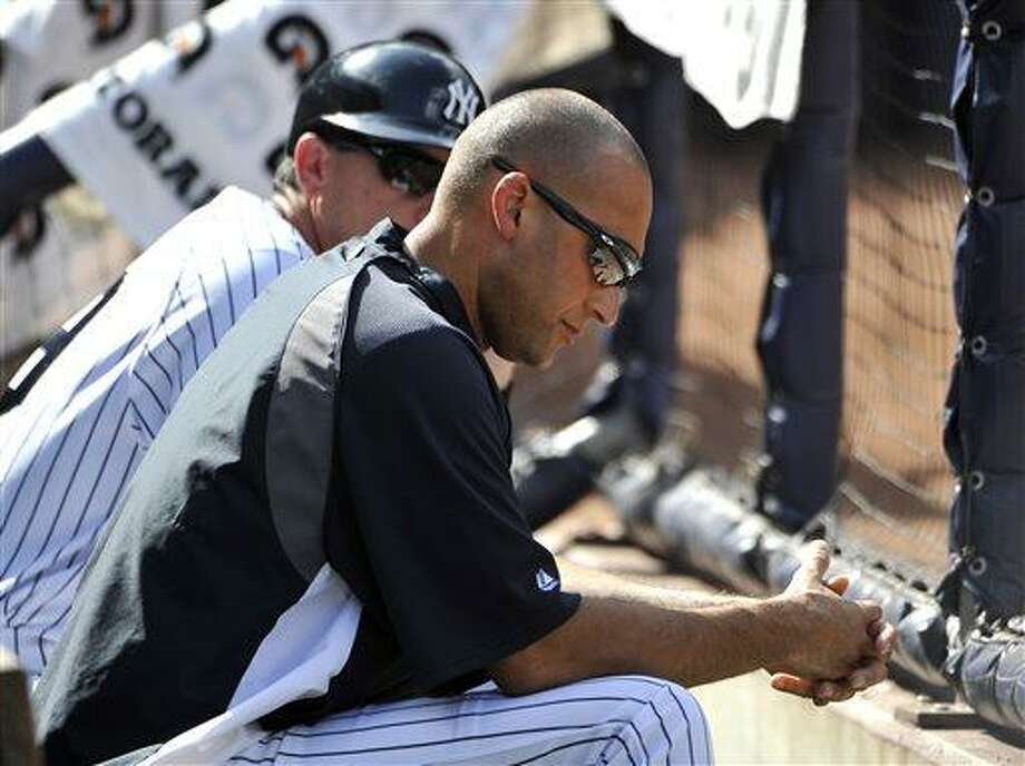 New York Yankees' Derek Jeter watching the game against the Minnesota Twins from the dugout in the eighth inning at Yankee Stadium on Sunday, July 14, 2013 in New York. Jeter is out with a strained quadricep. (AP Photo/Kathy Kmonicek) Photo: AP / FR170189 AP